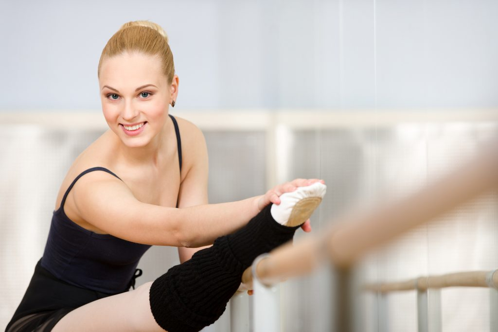 Athlete stretches herself near barre and mirrors in the classroo