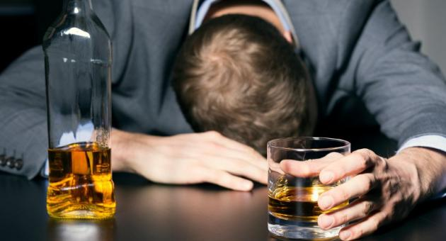 man with alcohol in hand and resting head on table - 6 λάθη που κάνετε και κάνουν το hangover σας πιο δύσκολο!
